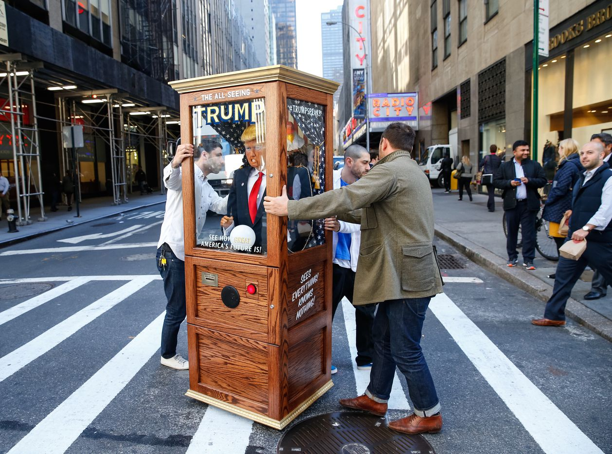 Artist Nathaniel Lawlor received some help from friend Jason Goodman as they pushed a fortune teller machine bearing Republican presidential candidate Donald Trump outside the Midtown Hilton in New York City on Tuesday, Nov. 8, 2016. When the red button was pushed, Trump's voice recited some of his famous and funny lines.