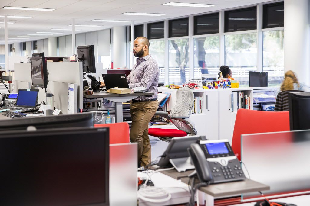 Javier Moreno, Toyota's manager of external affairs and communications, works at a standing workstation furnished by Knoll. (Smiley N. Pool/The Dallas Morning News)
