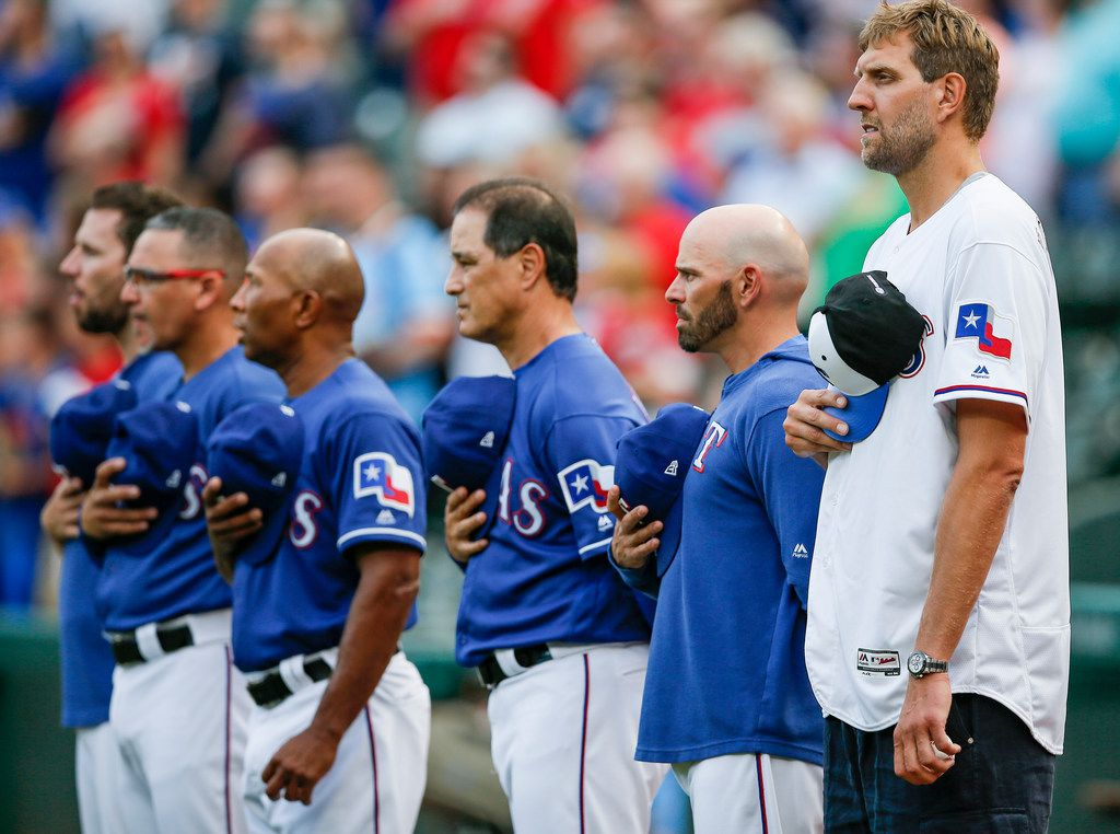 Former Dallas Mavericks player Dirk Nowitzki, far right, stands with Texas Rangers manager Chris Woodward, second from right, and the Rangers coaching staff during the National Anthem before a baseball game between the Baltimore Orioles and Texas Rangers, Wednesday, June 5, 2019, in Arlington, Texas. Nowitzki threw the first pitch. (AP Photo/Brandon Wade)