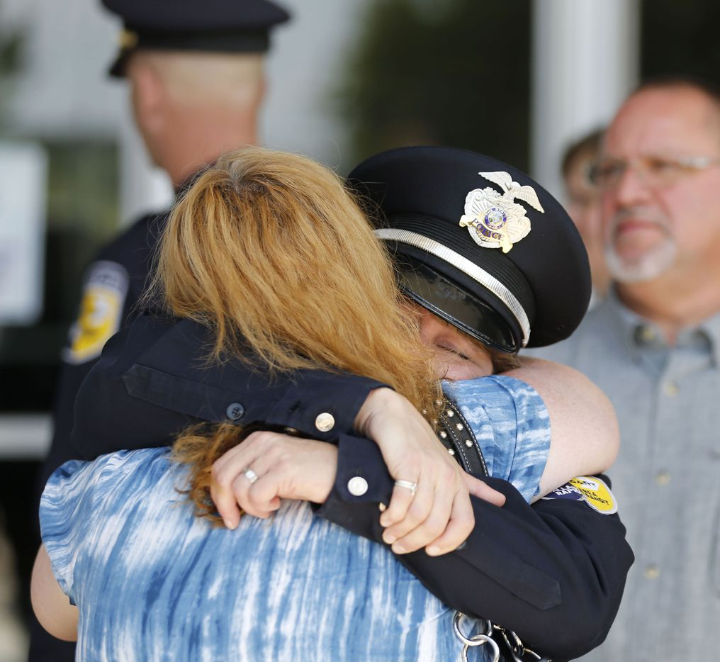 A DART officer hugs a person after a memorial service for DART Officer Brent Thompson at The Potter's House in Dallas on Wednesday, July 13, 2016. Thompson was one of five officers killed last week when a gunman opened fire during a Black Lives Matter rally in downtown Dallas.