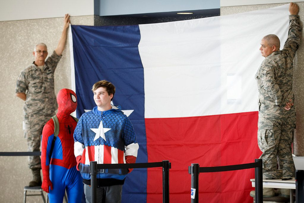 Two costumed young volunteers wait to check in as Texas National Guardsmen hold up a Texas flag for the backdrop of a press conference at the evacuation center at NRG Center on Monday, Sept. 4, 2017, in Houston. A group of elected officials met with evacuees and held a brief news conference in an effort to drum up support for emergency aid for Harvey victims.