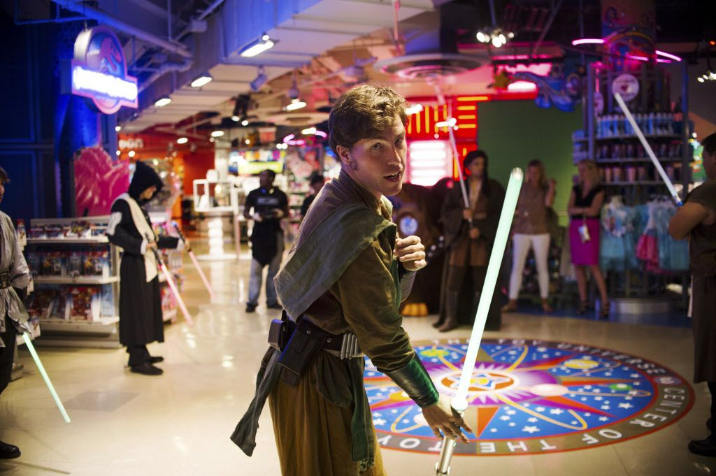 "Steven Cohen, in costume, practices moves with a light saber while waiting for customers to enter Toys ""R"" Us during the rollout of toys for the new ""Star Wars"" film, at Times Square in New York, Sept. 4, 2015."