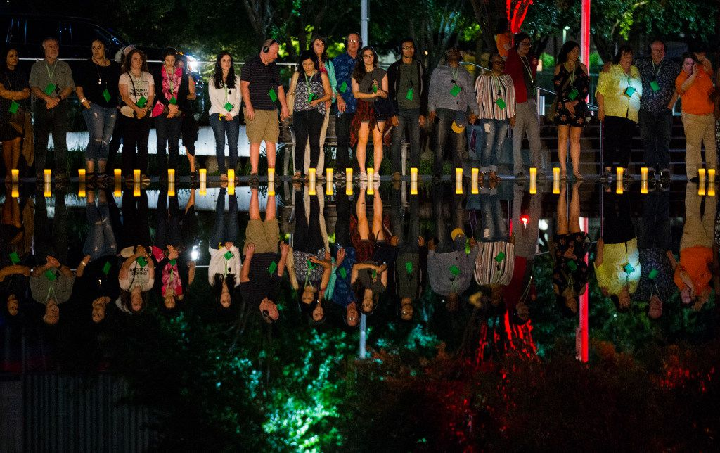 The audience places candles in a reflecting pool during a performance of Electra on  April 4, 2017 in Annette Strauss Square at the AT&T Performing Arts Center in Dallas