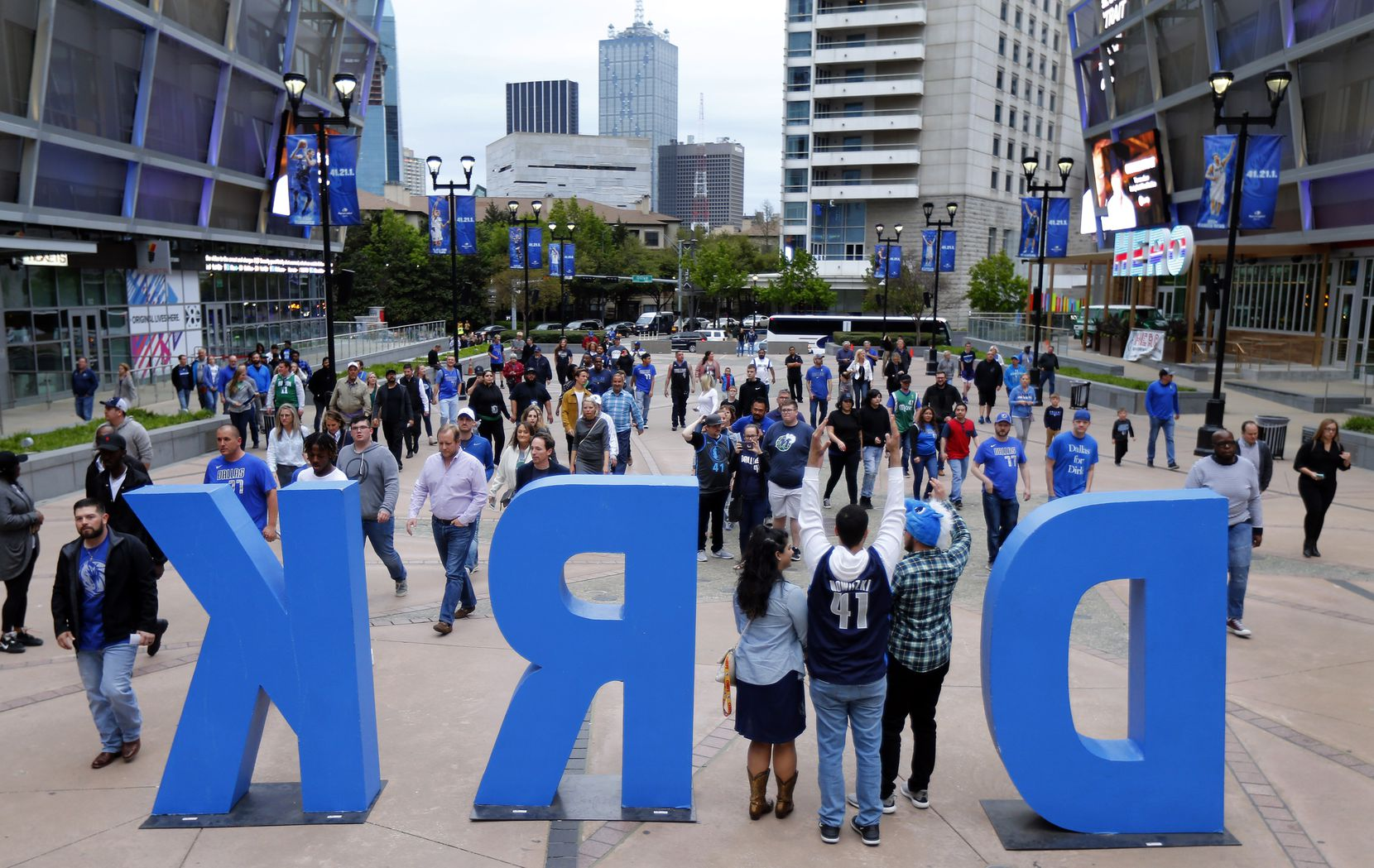 Dallas Mavericks fans pose for photos in the DIRK sign outside American Airlines Center in Dallas on April 3, 2019, before the Mavs played the Minnesota Timberwolves.