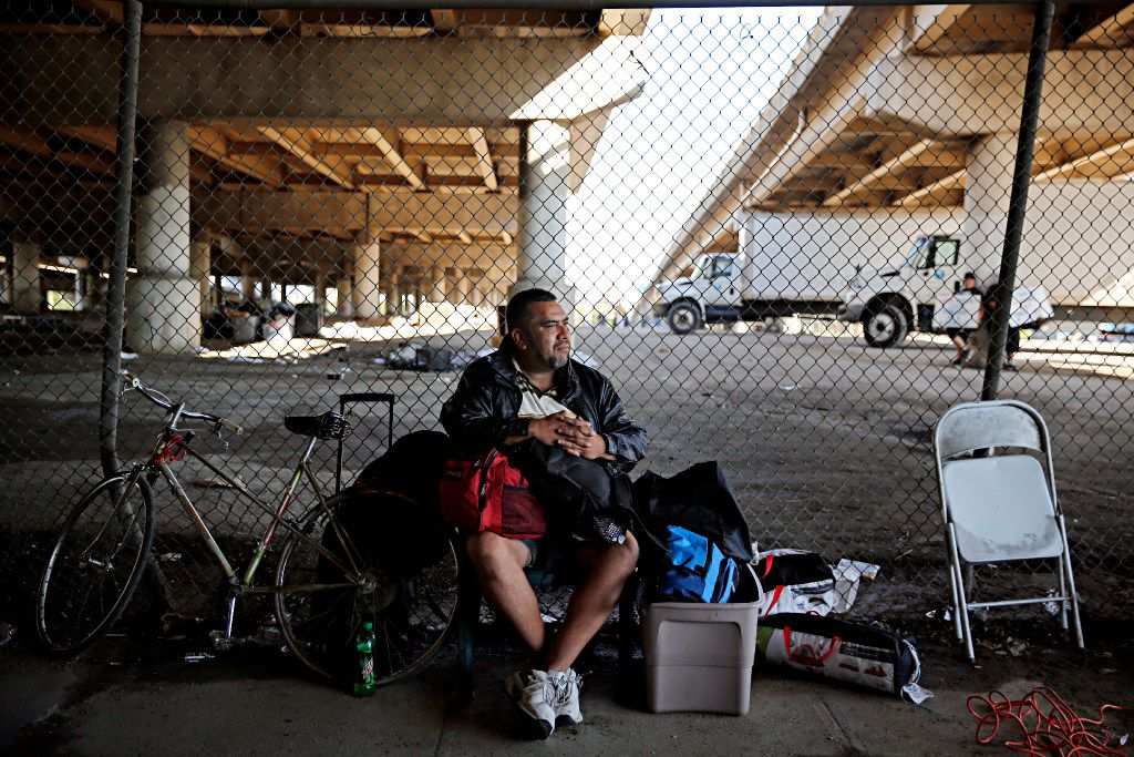 "A man who called himself ""J.R."" sits with his belongings outside the now gated Tent City Tuesday, May 3, 2016 in Dallas. The final two sections of the contentious homeless encampment where closed Tuesday morning, sending the remaining residents scrambling for shelter. J.R. said he has been living in Tent City for two months. (G.J. McCarthy/The Dallas Morning News)"