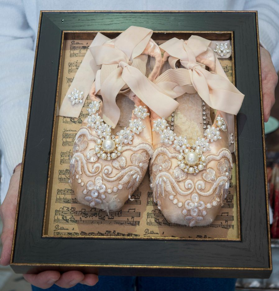 Lynn Teeling, owner of pop-up Sweet Pickins, holds a pair of embellished, framed pointe shoes.