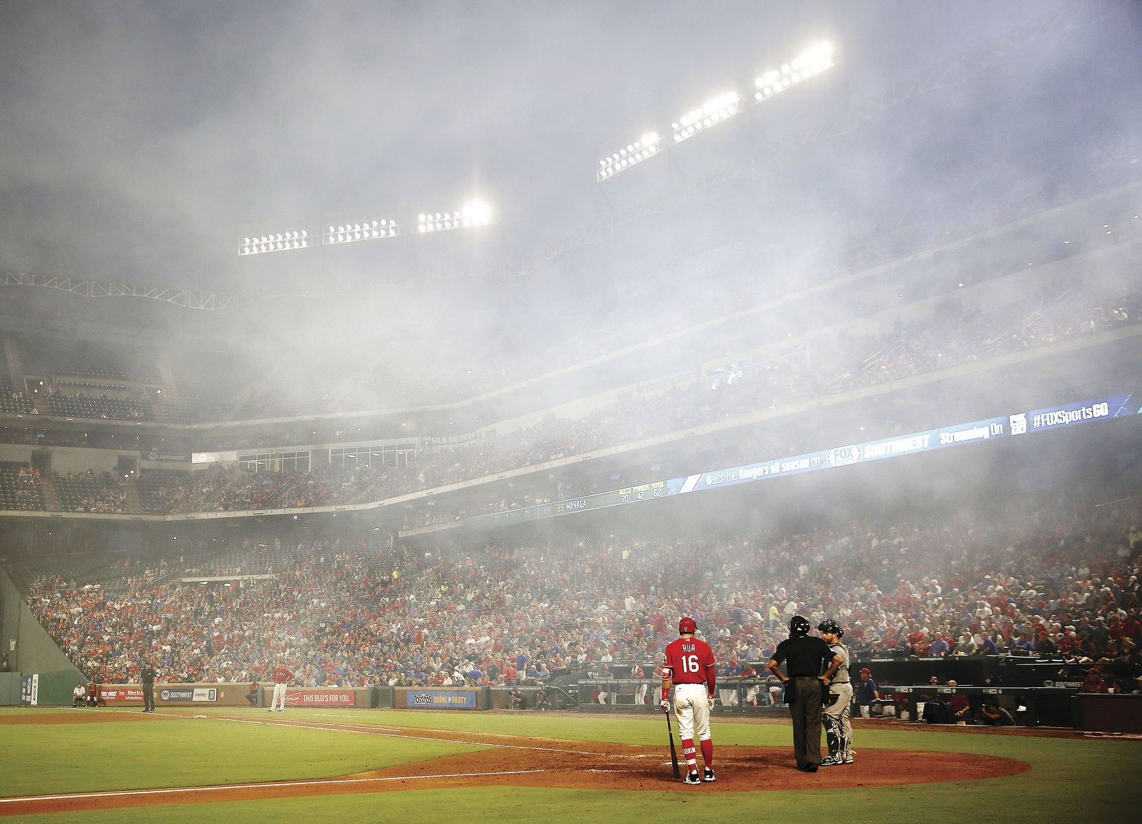 Texas Rangers left fielder Ryan Rua waited to bat as the smoke from the fireworks following a solo home run by catcher Jonathan Lucroy dissipated in the fourth inning of a game against the Oakland Athletics at Globe Life Park in Arlington on Aug. 17. The Rangers won that game and 94 others en route to the best regular-season record in the American League.