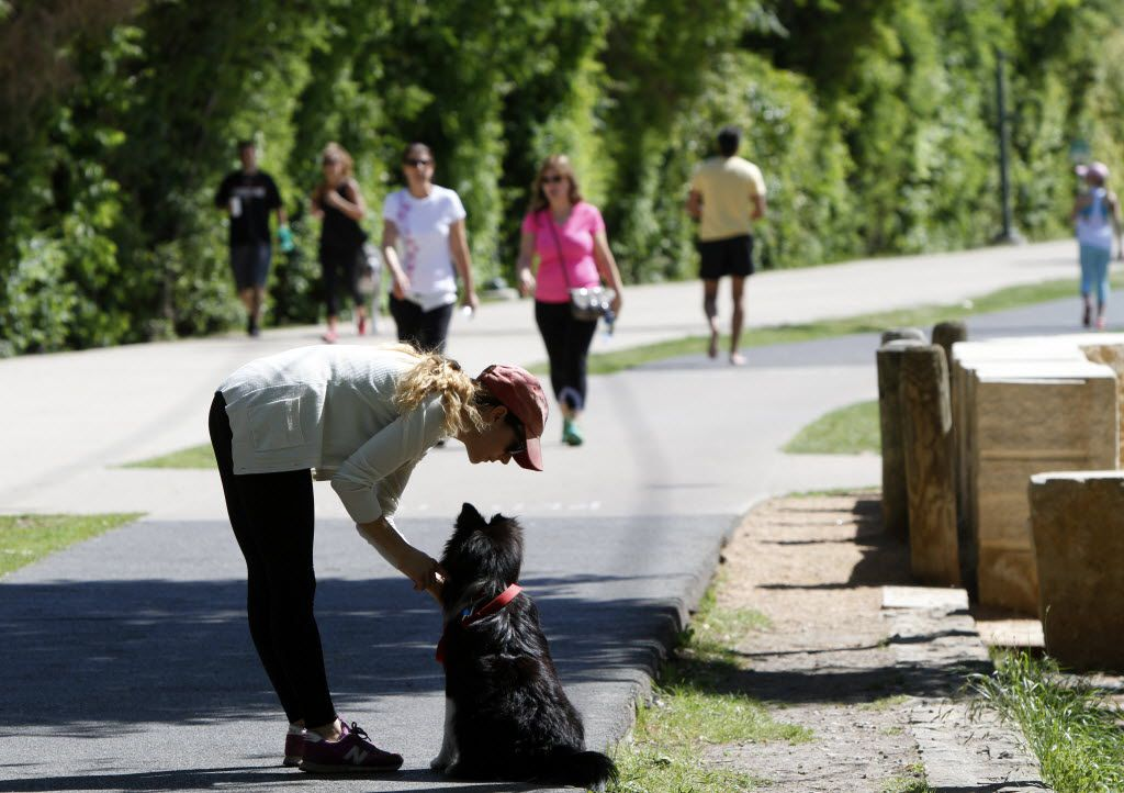 Monica Chavez, 32, praises her dog Enzo for not barking at a passing rollerblader during their walk on the Katy Trail. The city is planning on connecting trails throughout Dallas to form one big circuit of trails. The 2017 bond package would use public money in combination with privately raised funds to construct the circuit trail (Ben Torres/Special Contributor)