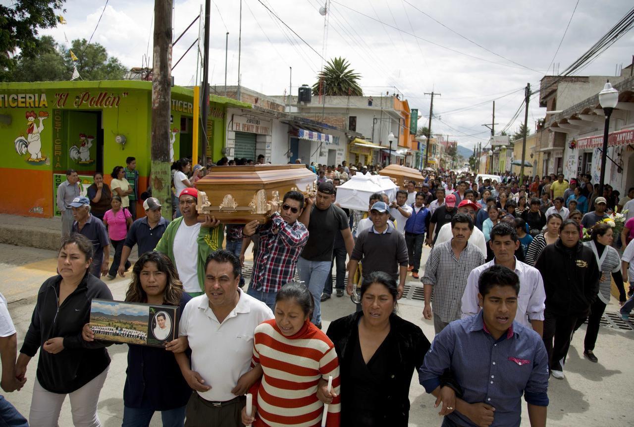 Dolientes cargan los féretros de tres personas fallecidas durante los enfrentamientos enter maestros y polidías el fin de semana en Nochixtlán, Oaxaca. (AP/EDUARDO VERDUGO)
