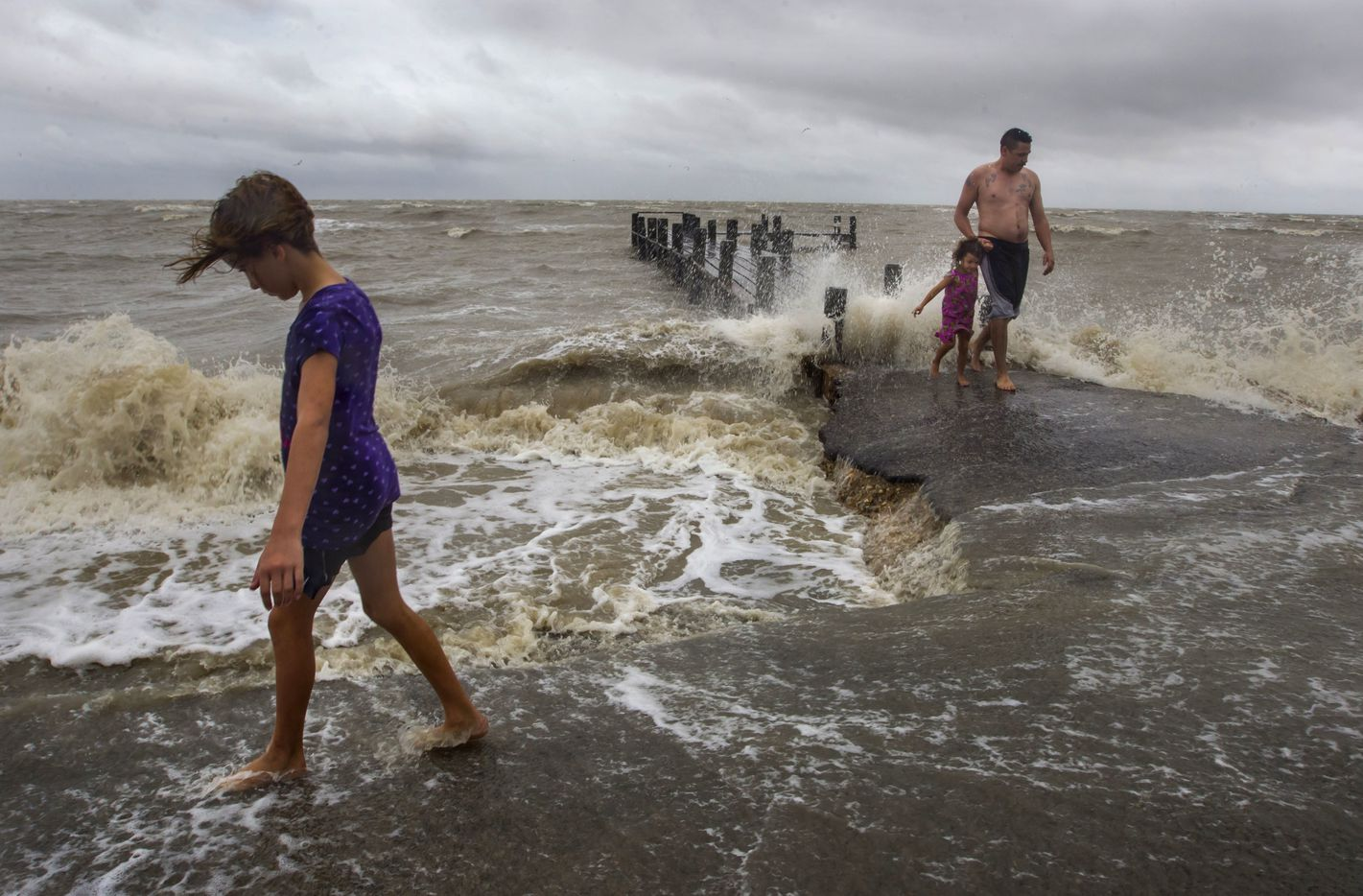 Serenity McGinnis, 10, walks along the shore with her father Jesse and sister Rebella, right, near a pieras Hurricane Harvey approaches the Texas coast Friday, Aug. 25, 2017 in Bacliff, Texas. Harvey intensified into a hurricane Thursday and steered for the Texas coast with the potential for up to 3 feet of rain, 125 mph winds and 12-foot storm surges in what could be the fiercest hurricane to hit the United States in almost a dozen years.