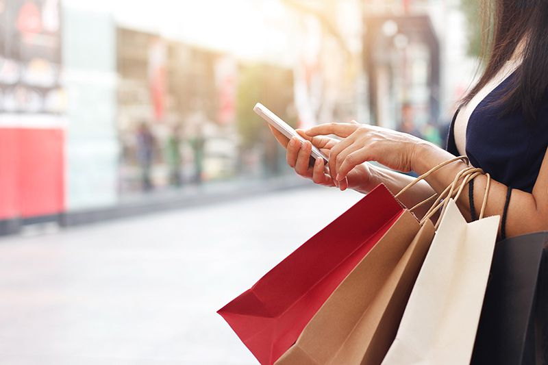 Woman using smartphone and holding shopping bag while standing on the mall background