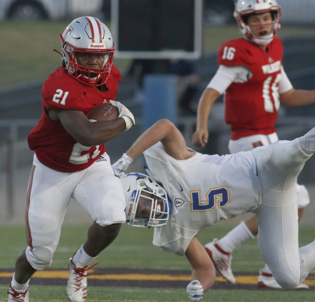 Dallas Woodrow Wilson running back Matthew Jackson (21) cuts upfield after avoiding the pursuit of Frisco defender Jacob Stayman (5) during a first half rush.  The two teams competed in their season-opening non-district football game at Franklin Stadium in Dallas on August 29, 2019. (Steve Hamm/ Special Contributor)