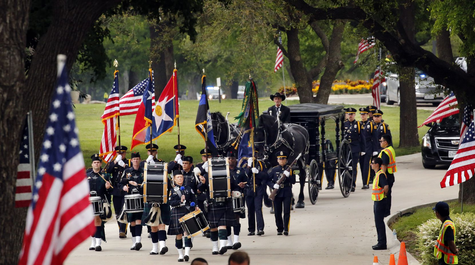 The Dallas Police Color Guard and Honor Guard escort the horse-drawn carriage carrying slain Dallas police officer Rogelio Santander, Jr. to his resting place in the Garden of Honor at Restland Funeral Home and Cemetery in Dallas, Tuesday.