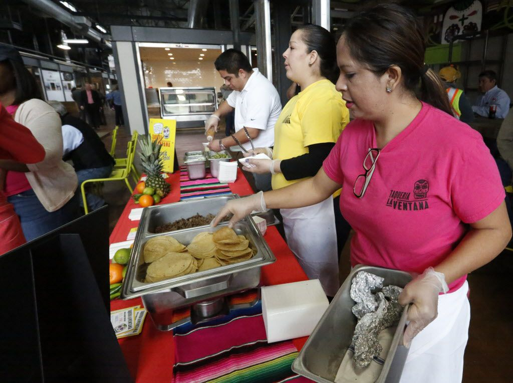 From left, back to front, Hugo Miranda, Cynthia Fernandez and Maria Moreno kept the tacos flowing at the Taqueria La Ventana booth at The Market's soft opening at the Dallas Farmers Market  Friday December 11, 2015.  (Ron Baselice/The Dallas Morning News)   [ This is located in the building formerly called Shed 2 at the Dallas Farmers Market ]