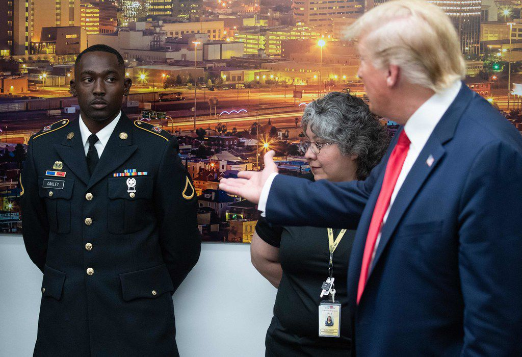 US President Donald Trump (R) gestures to PFC Glendon Oakley (L), who saved several lives during a mass shooting in Texas, during a visit to El Paso Regional Communications Center in El Paso, Texas, August 7, 2019.