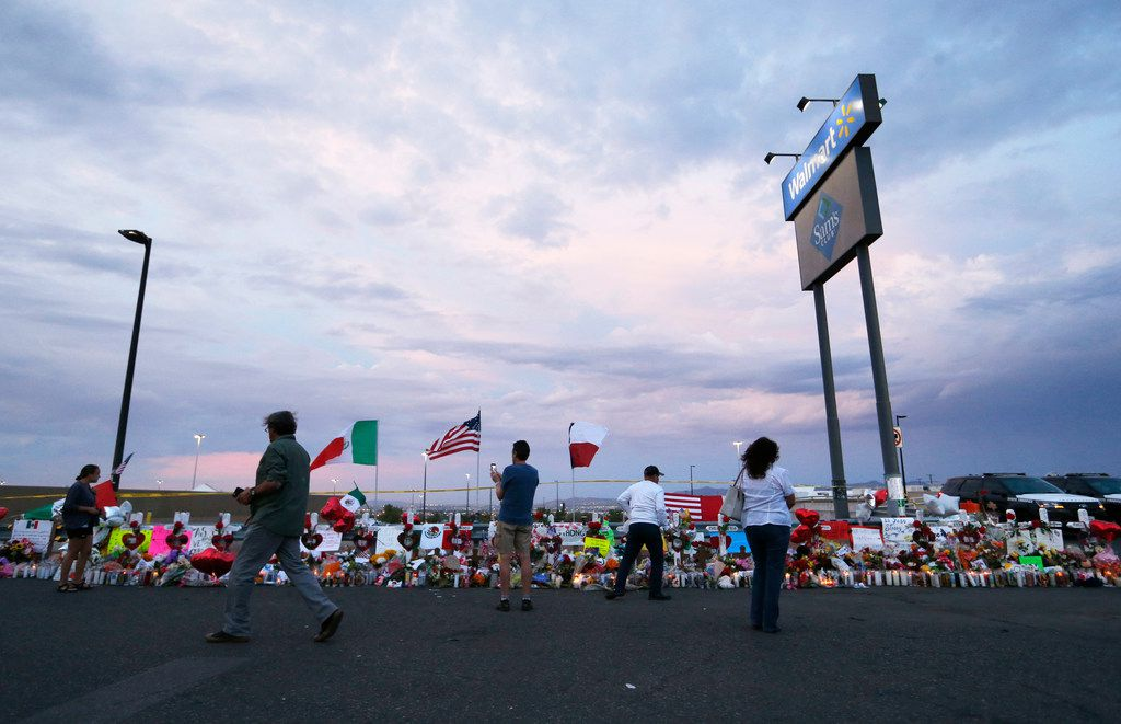 People stood next to 22 crosses Tuesday at a makeshift memorial for victims of Saturday's mass shooting at an El Paso Walmart. On Thursday, a man allegedly armed with a gun and knife was detained in front of a migrant community center, putting the city's residents further on edge.