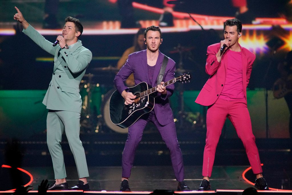 """Nick Jonas, from left, Kevin Jonas and Joe Jonas, of the Jonas Brothers, perform during their """"Happiness Begins"""" tour at the United Center on Thursday, Sept. 19, 2019, in Chicago."""