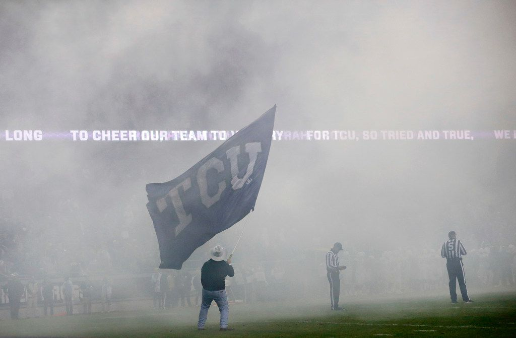 Smoke from pyrotechnics fill the stadium, as a TCU Rangers member waves the school flag  following a touchdown against the West Virginia Mountaineers at Amon G. Carter Stadium in Fort Worth, Friday, November 29, 2019. The Horned Frogs lost though, 20-17. (Tom Fox/The Dallas Morning News)