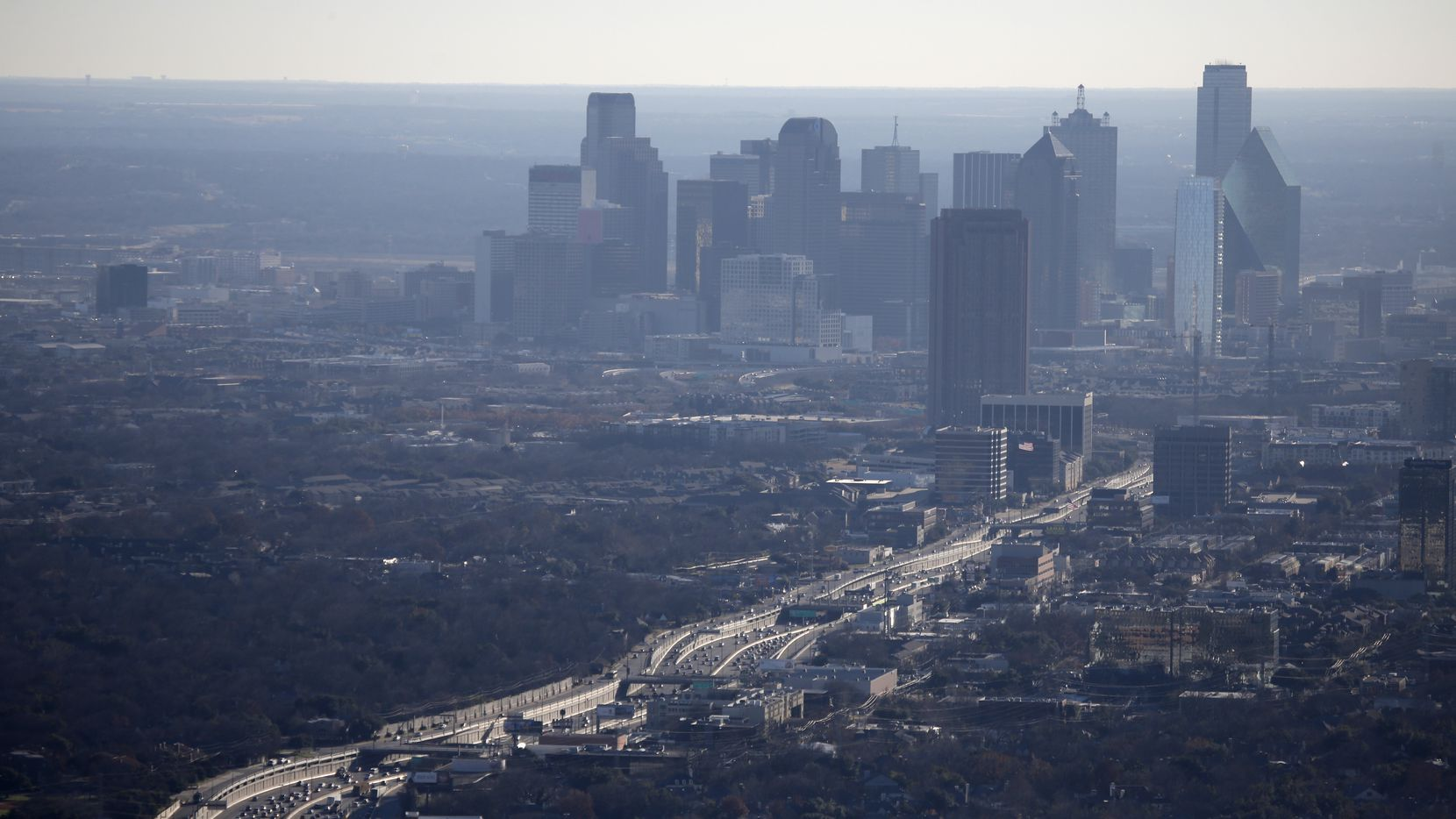 The air hangs with haze as traffic moves on Hwy. 75 Central Expressway from near the Mockingbird Lane (not pictured, bottom) area to downtown Dallas (top) January 3, 2014. CityPlace tower stands in the foreground (center right), north of downtown.