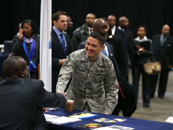 Air Force Master Sgt. Cecilio Ricardo visits a Department of Veterans Affairs booth while attending job fair for veterans and their spouses.
