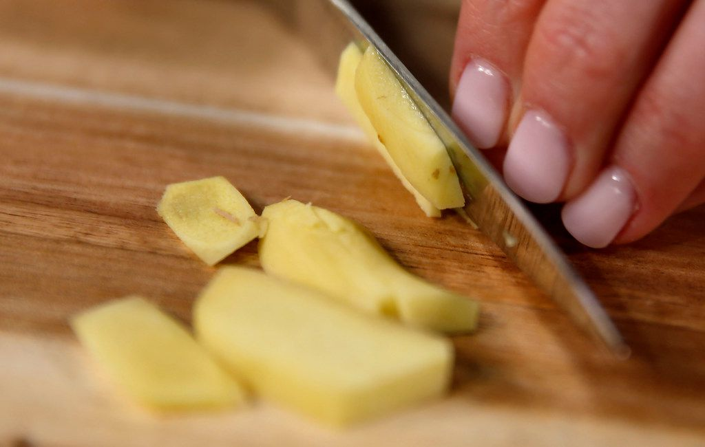Rebecca White slices ginger while she demonstrates how to make turmeric latte in The Dallas Morning News studio.