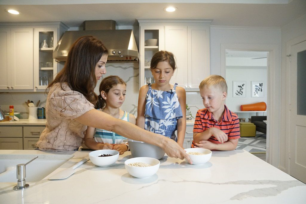 Kristen Massad preparing granola bars with her daughters Adele Massad (6) and Sophie Massad (8) and a family friend Sam Booke (6) at her home in Dallas.