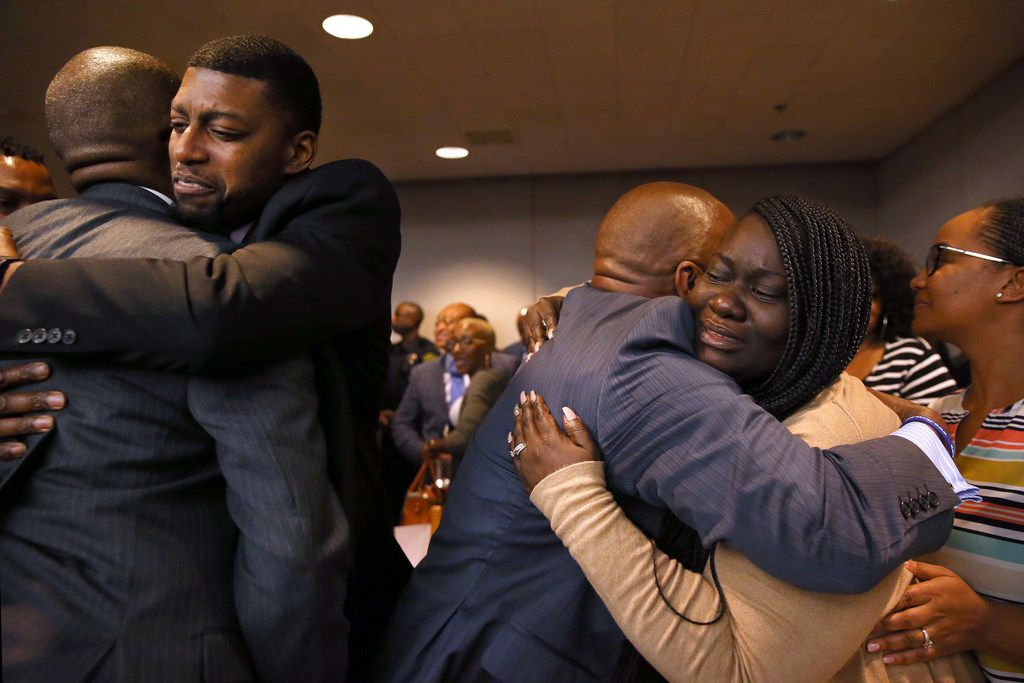 The parents of Jordan Edwards, Odell and Charmaine Edwards (facing camera), hug prosecutor George Lewis (left) and family member Reggie Edwards (right) as they react to a guilty verdict during the trial of fired Balch Springs police Officer Roy Oliver.