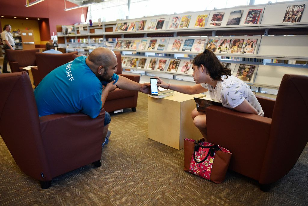 Victor Moreno, 26, (left), showed his girlfriend, Cameron Dahlia, 20, a job listing on his phone as he searched for jobs while using the free Wi-Fi at the Pleasant Grove Branch Library on Friday.