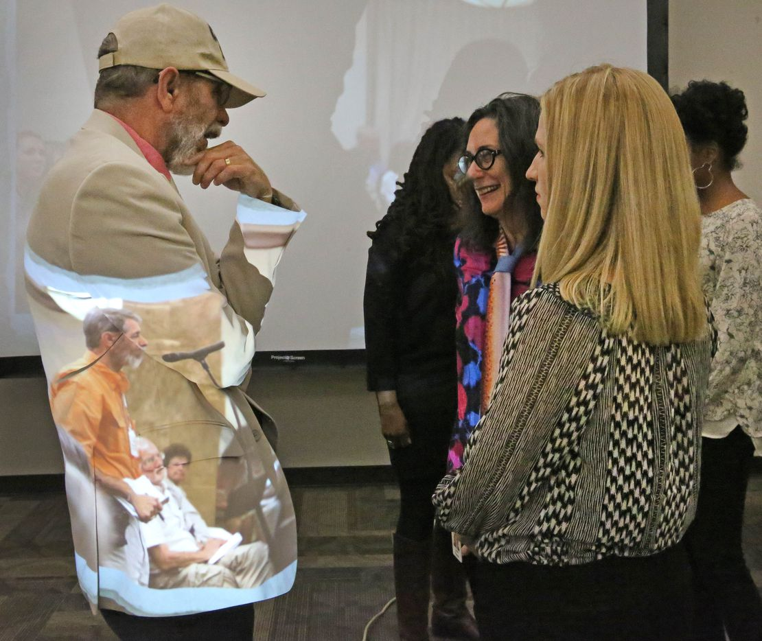 Co-workers of Jeffrey Weiss gather to wish him well at his career tribute party, as a projector displays images from Weiss' career at The Dallas Morning News on Wednesday, March 1, 2017. (Louis DeLuca/The Dallas Morning News)