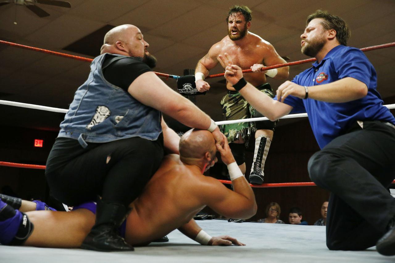 Moonshine Mantell (arriba al centro) anima a su compañero Killer McKenzie, mientras este somete a Seth Allen durante una lucha de parejas en Sherman Elks Lodge, en Sherman. (DMN/ANDY JACOBSOHN)