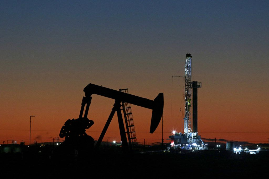 In this Tuesday, Oct. 9, 2018, photo, an oil rig and pump jack are at work as seen from the roadside of FM 1788 in Midland, Texas. (Jacob Ford/Odessa American via AP)