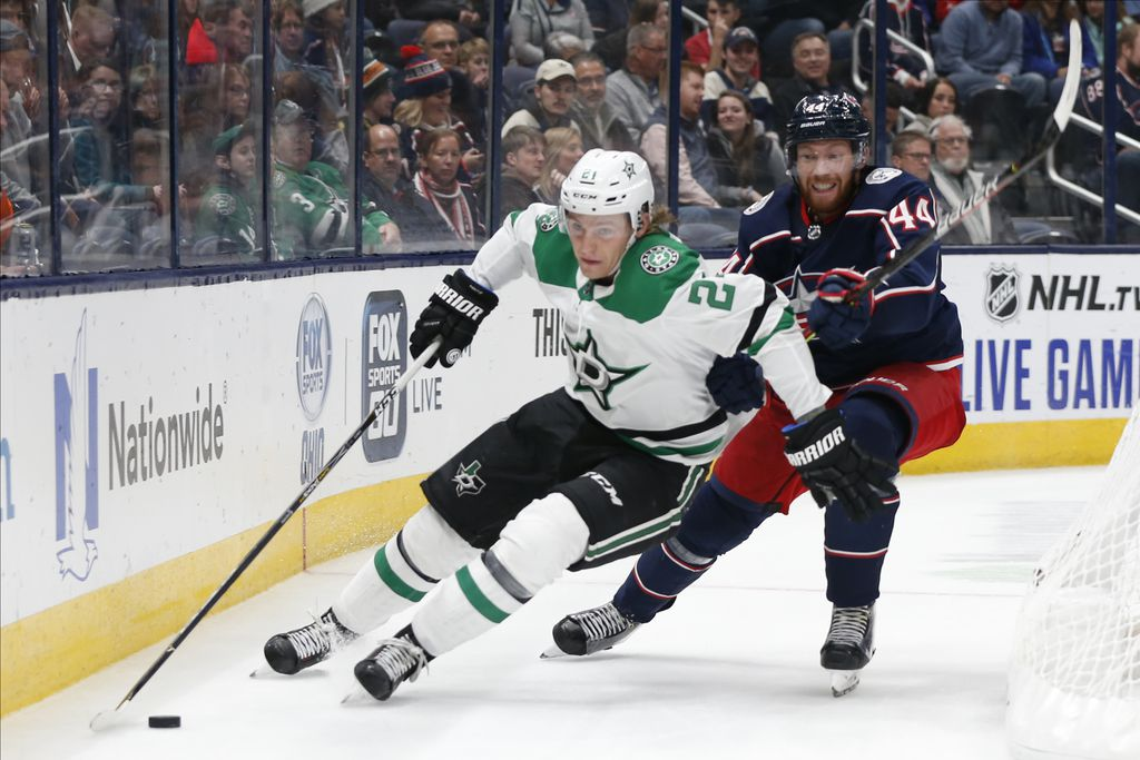 Dallas Stars' Roope Hintz, left, of Finland, carries the puck behind the net as Columbus Blue Jackets' Vladislav Gavrikov, of Russia, defends during the third period of an NHL hockey game Wednesday, Oct. 16, 2019, in Columbus, Ohio. The Blue Jackets won 3-2. (AP Photo/Jay LaPrete)