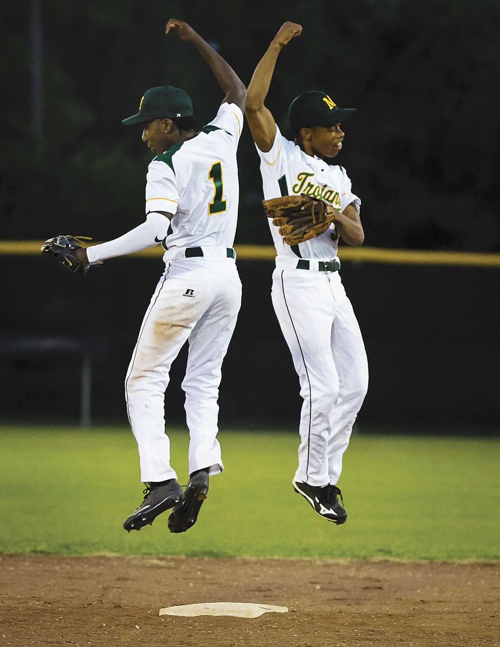 Madison High second baseman David Butler (left) and shortstop Juriod Hollie do a leaping high five as they take the field in the third inning against Kemp at Pleasant Grove Baseball Stadium.