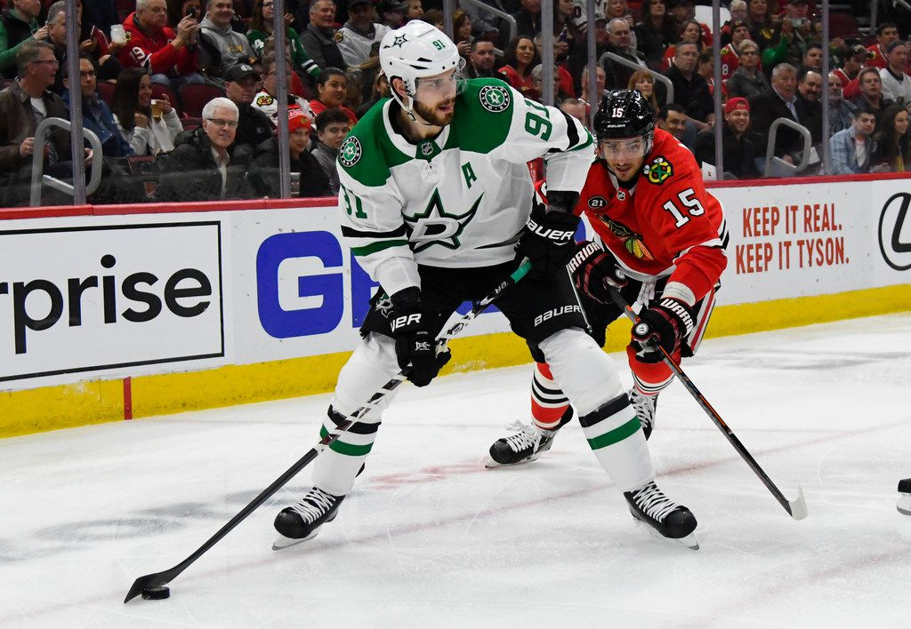 Dallas Stars center Tyler Seguin (91) moves the puck against Chicago Blackhawks center Artem Anisimov (15) during the first period of an NHL hockey game Friday, April 5, 2019, in Chicago. (AP Photo/Matt Marton)