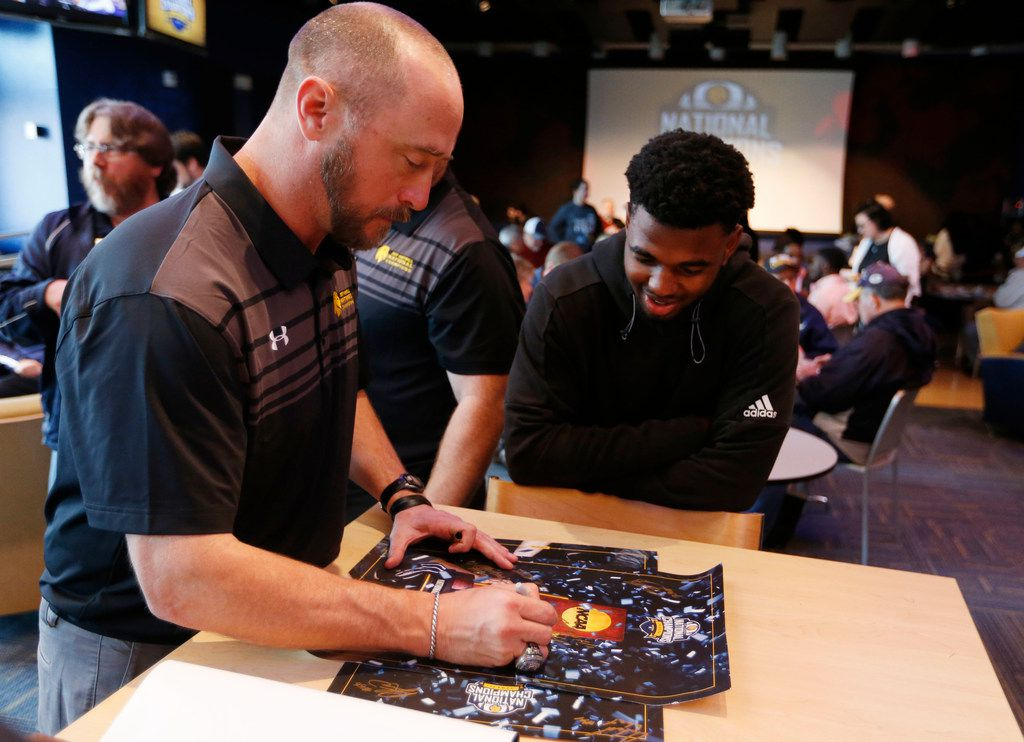 FILE - Texas A&M University-Commerce head football coach Colby Carthel signs a poster for football player Rashad Fisher during a celebration of their recent national championship in Division II NCAA football at Texas A&M University-Commerce in Commerce, Texas on Friday, January 26, 2018. (Vernon Bryant/The Dallas Morning News)