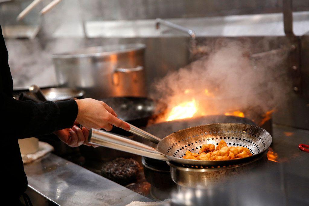 Jonathan Orihuela, wok cook, prepares a meal.