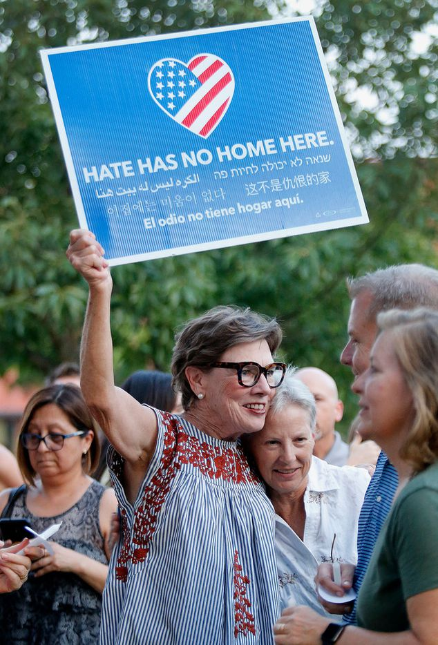 Susie Macheimehl (left) of McKinney, holds a sign while embracing Wendy Hunter of McKinney during a candle light vigil held at Dr. Glenn Mitchell Memorial Park in McKinney on Monday, August 5, 2019, for the victims of recent shootings.
