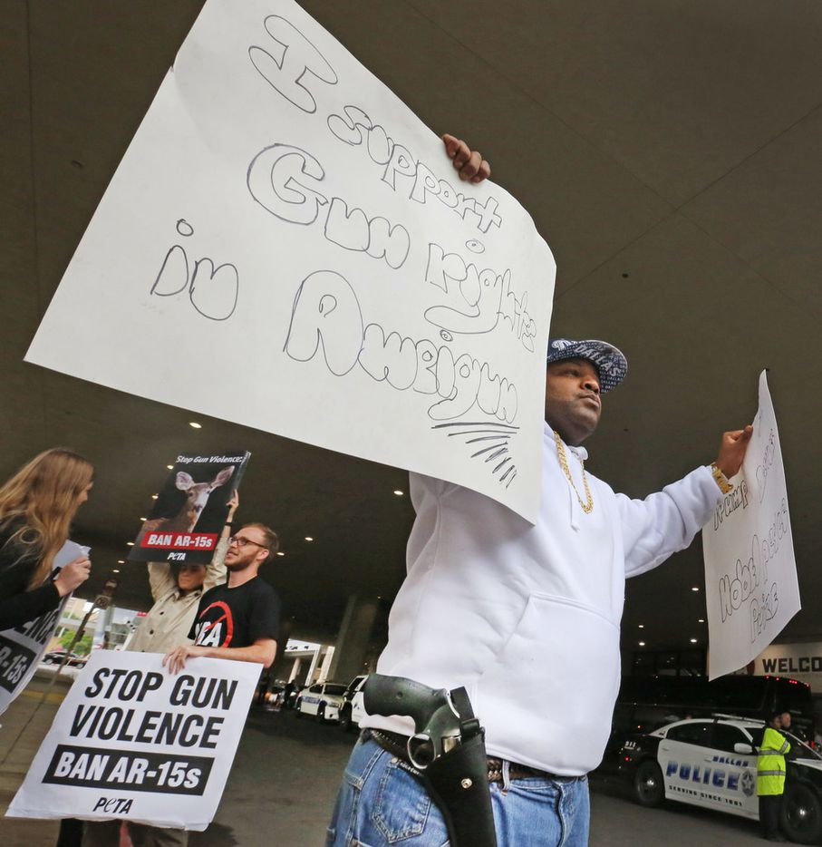 Jonathan Davis, a Navy veteran advocating gun ownership, has a pistol in a holster at his side as he holds signs outside the NRA Convention at the Kay Bailey Hutchinson Convention Center in downtown Dallas on Friday, May 4, 2018.  (Louis DeLuca/The Dallas Morning News)