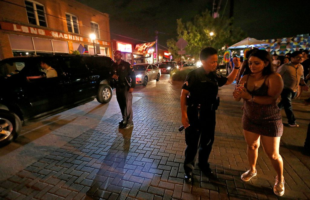 Detective Charita Grider helps Alina Bhattarai find a bar Friday while Detective Michael Mulkey directs traffic while patrolling Deep Ellum.