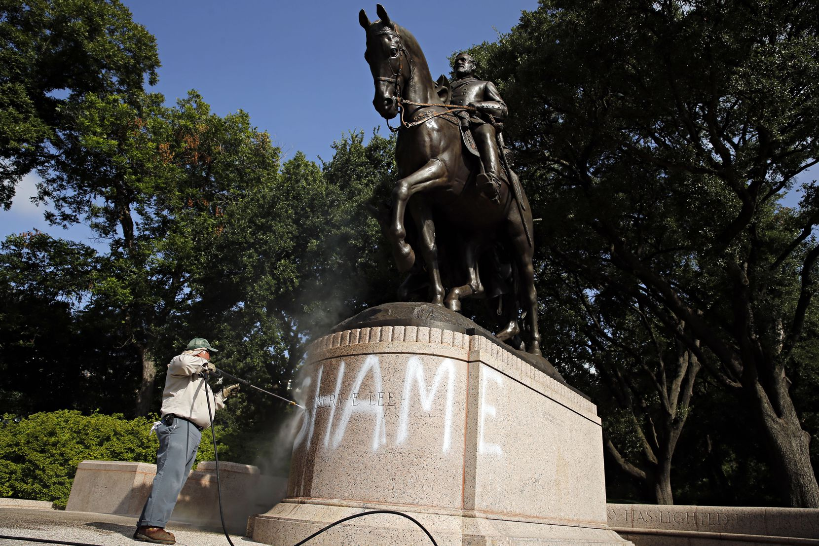 "Tino Banda with the Dallas Park and Recreation Department used a power washer to remove the spray-painted word ""SHAME"" from a statue of Gen. Robert E. Lee at Lee Park in June 2015."