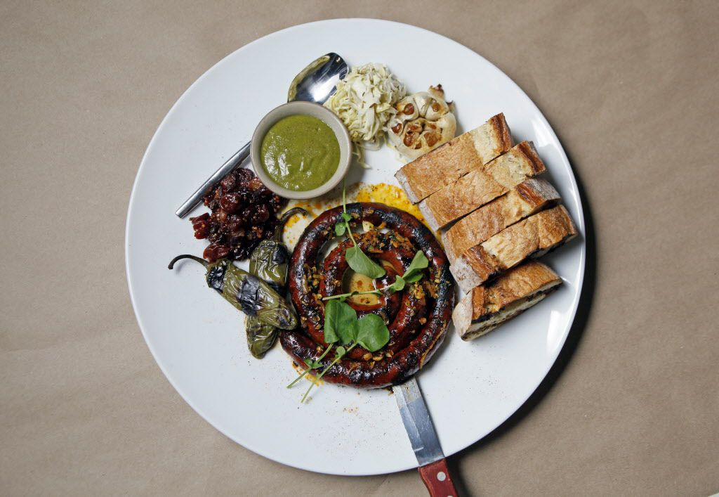 Grilled sausage by the yard with green chile mustard, dried fruit relish,  rustic toast and caraway cabbage