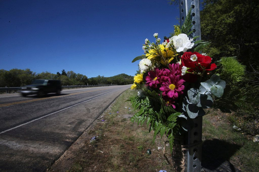 Flowers are placed on a road sign where 13 people died in Wednesday's head-on collision involving a truck and a bus of First Baptist Church of New Braunfels, near Leakey, Texas, Thursday, March 30, 2017. Law enforcement officials from two departments say they received phone calls about the pickup truck driving erratically shortly before a collision between the truck and the church bus in southwest Texas that killed 13 people returning from a retreat. (John Davenport/The San Antonio Express-News via AP)