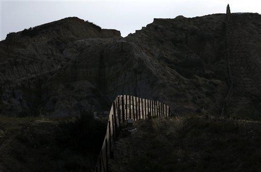 En esta imagen de archivo del 22 de junio de 2016, la luz ilumina un tramo de la cerca que separa Tijuana, México, y San Diego, Estados Unidos. (AP/GREGORY BULL)