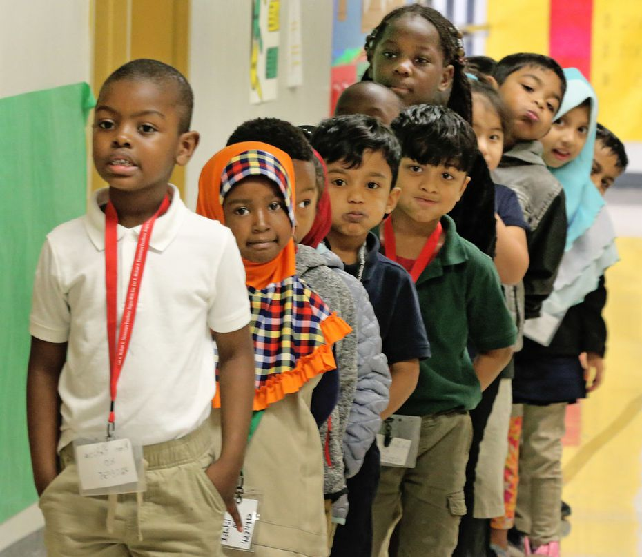 Kim Hakiza leads the line of Adrian Rivera's kindergarten class as they wait in the hallway at Dallas ISD's McShan Elementary in Vickery Meadow.