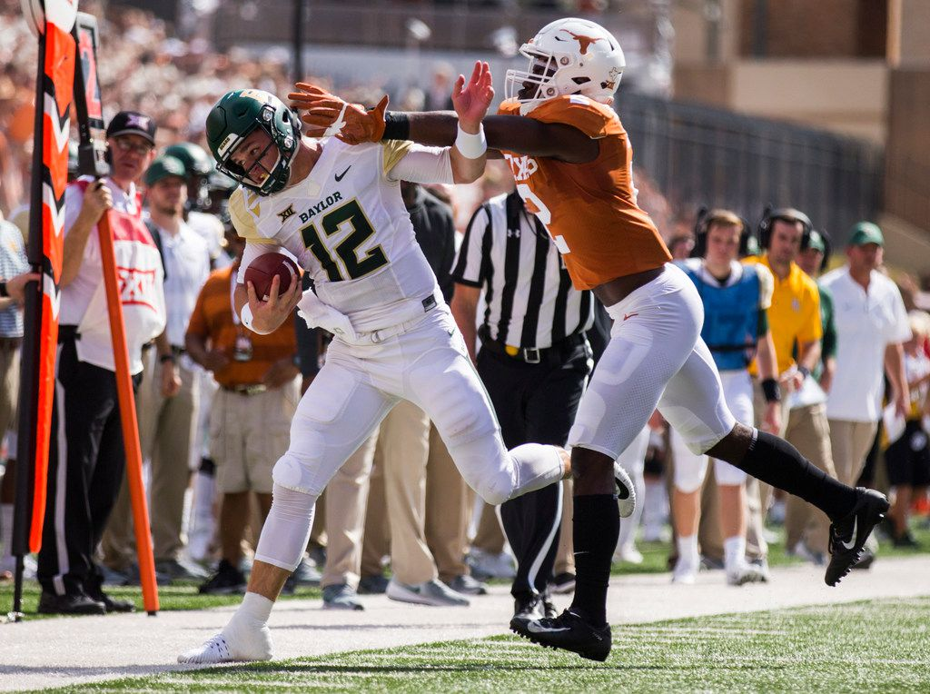 Baylor Bears quarterback Charlie Brewer (12) is pushed out of bounds by Texas Longhorns defensive back Kris Boyd (2) during the first quarter of a college football game between Baylor and the University of Texas on Saturday, October 13, 2018 at Darrell K Royal Memorial Stadium in Austin, Texas.  (Ashley Landis/The Dallas Morning News)