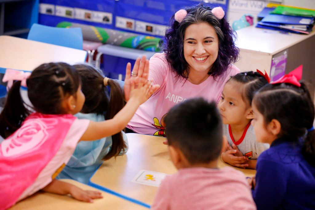 Among the things that a state budget tentatively approved by the Texas House late Wednesday would do is provide funding of full-day prekindergarten, if a separate bill overhauling school finance passes. In a March 2019 file photo, pre-K teacher Patricia Sifuentes gives a high-five to student Alexia Najera during a math center lesson at the newly opened Arlington Park Early Childhood Center in Dallas. (Tom Fox/The Dallas Morning News)