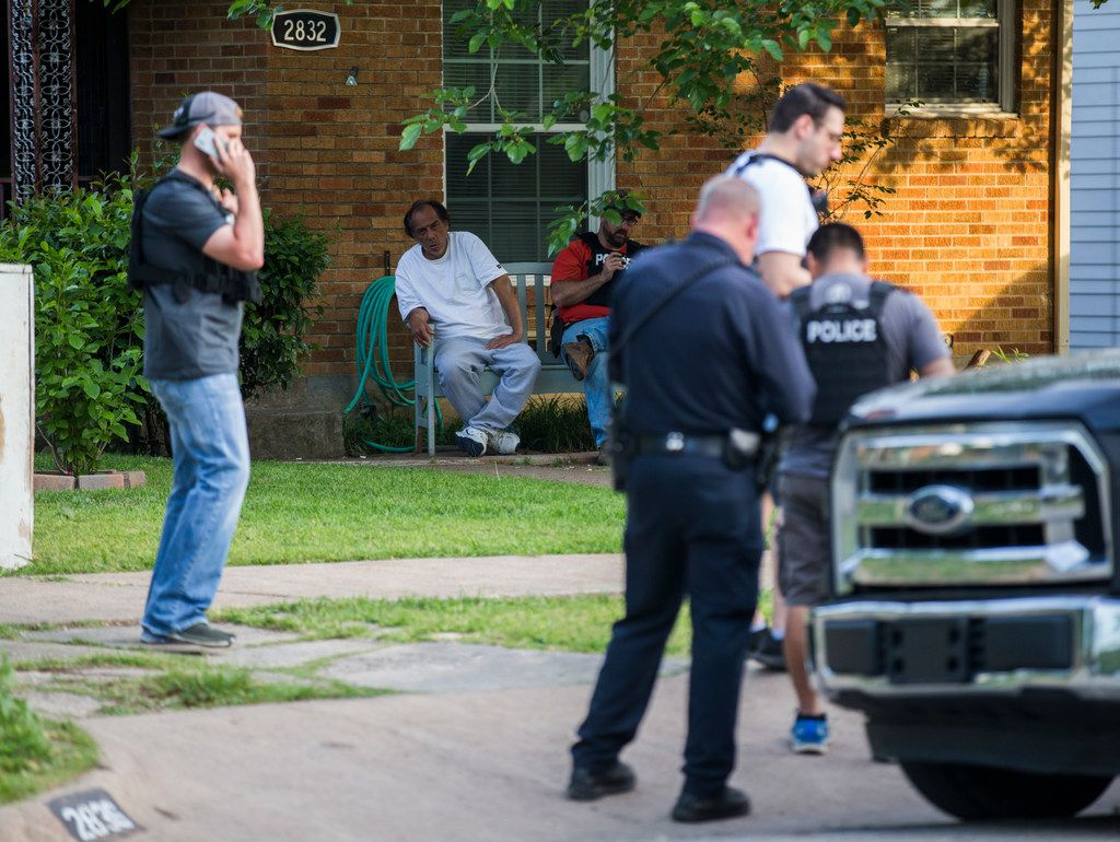 Police officers stand outside a home belonging to relatives of a man who shot two officers outside a Home Depot on Tuesday, April 24, 2018 on Hedgerow Dr in Dallas. (Ashley Landis/Staff Photographer)