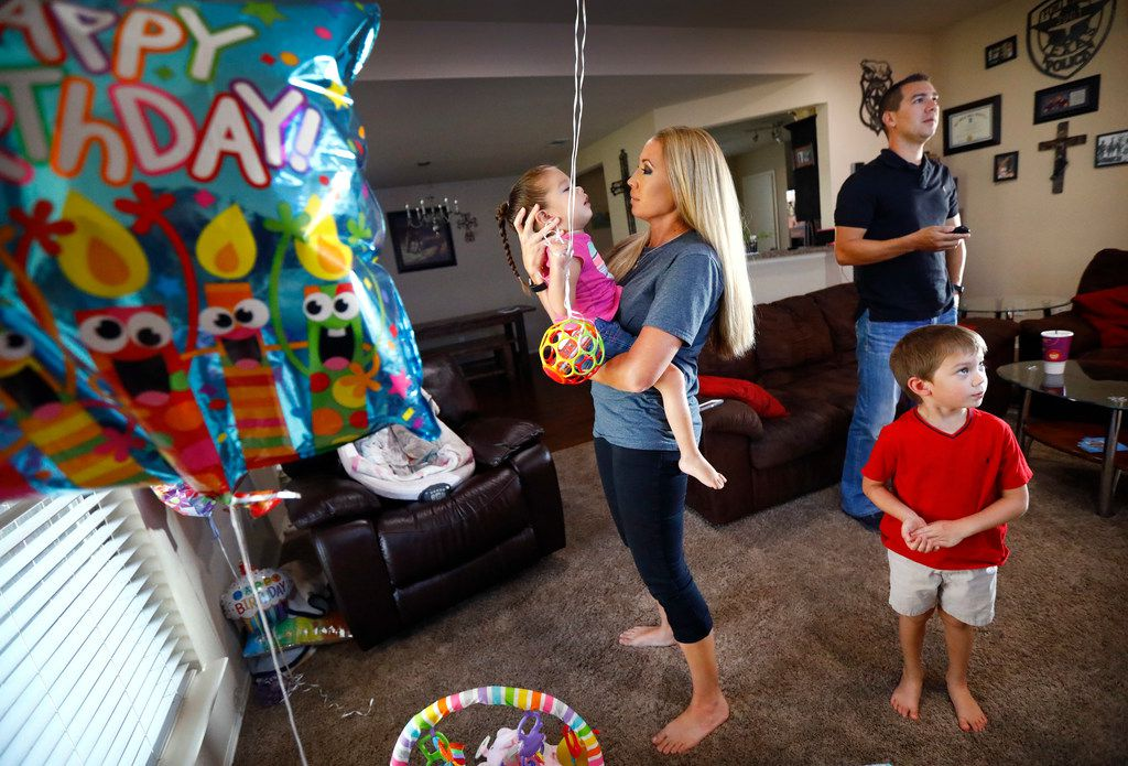 Jayme Magallon embraces her 3-year-old daughter Annalynne, who suffers from cerebral palsy, as they play among her birthday balloons. Her husband Brandon Magallon (right) and 4-year-old son Acetyn watch television at their Burleson home Friday, July 13. The Magallons are one of many families who say they've considered divorce so that their sick or disabled children can be cared for through the unemployed parent's Medicaid. The situation is informally advised to many Texas families.