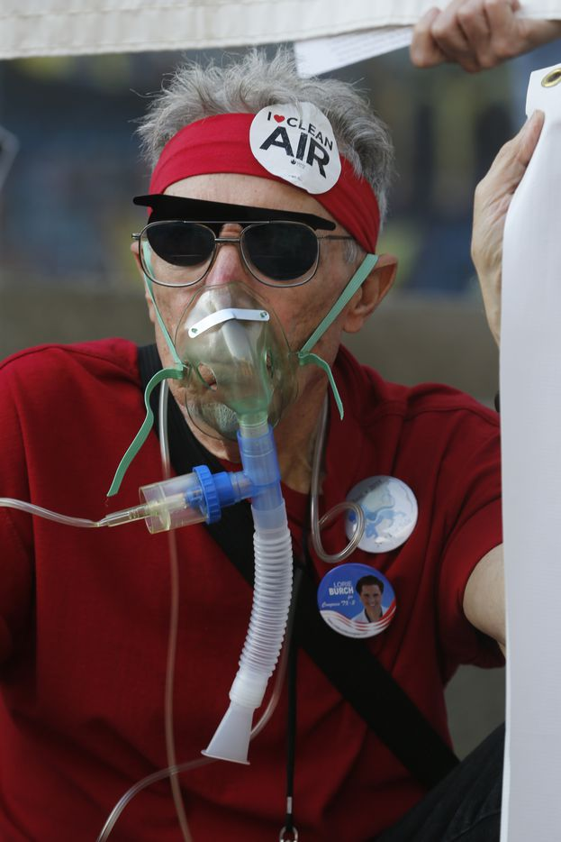 Zen Biasco wears a oxygen mask to make a statement as protesters gather outside of the Exxon shareholders meeting.  (Nathan Hunsinger/The Dallas Morning News)