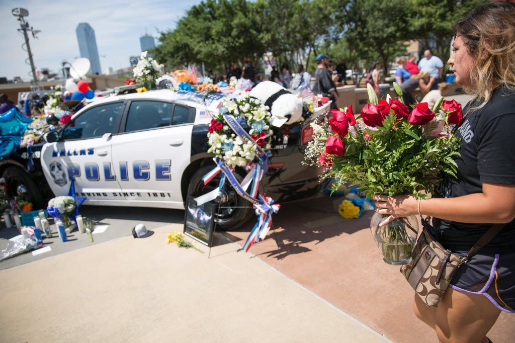 A woman added flowers to a memorial outside Dallas police headquarters on Friday, a day after a gunman opened fire on Dallas officers, killing five and wounding seven.